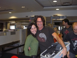 Stephanie Nye in the TSA holding pen, Rick Springfield holds his items at TSA